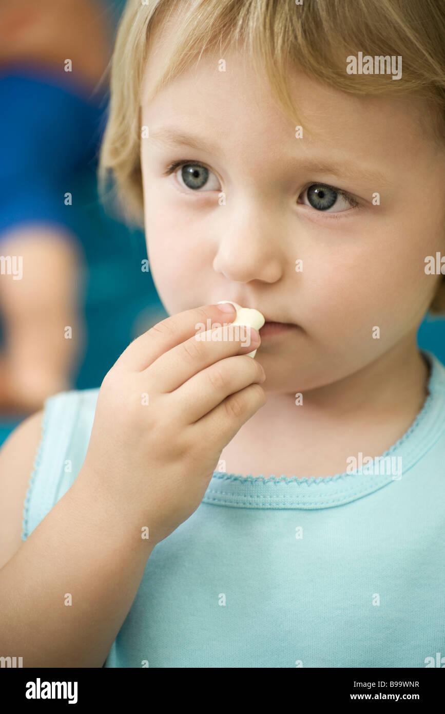 Little girl eating marshmallow - Stock Image