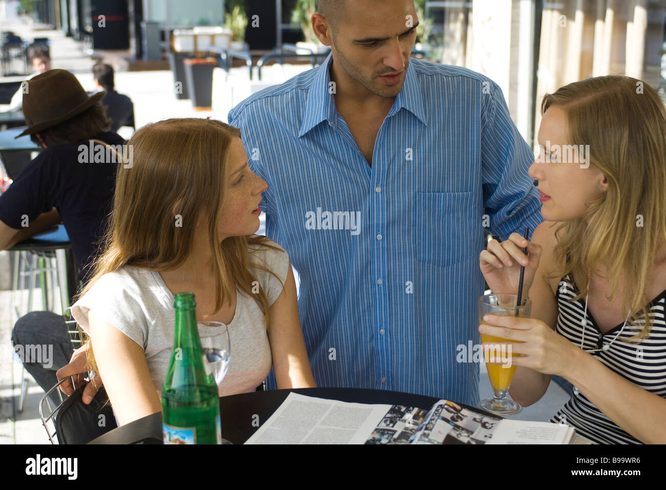 Man talking to two young women at outdoor cafe - Stock Image