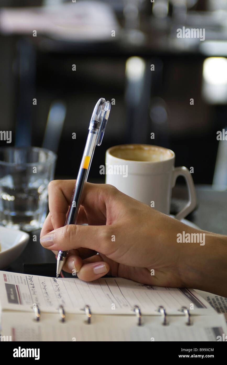 Woman sitting in cafe, writing in agenda, cropped view of hand - Stock Image