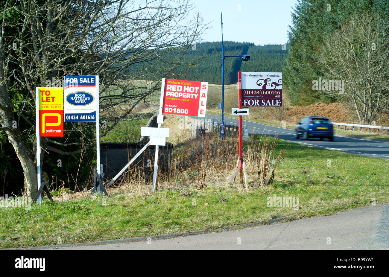 House 'For Sale' and 'To Let' signs by a road Stock Photo