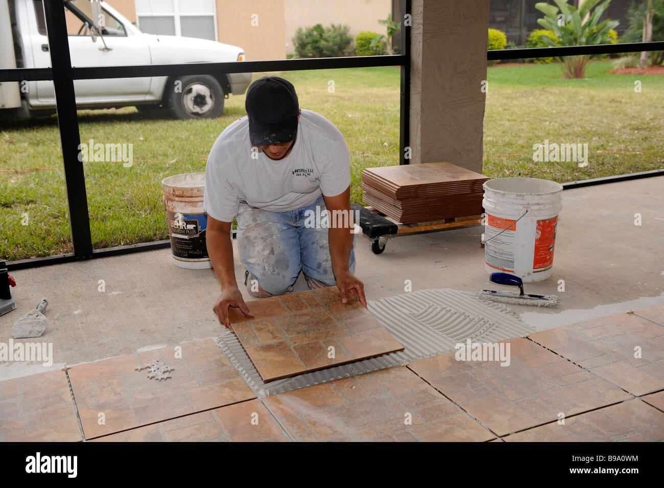 Charmant Male Hispanic Lays Ceramic Tile On Cement Floor In Patio Lanai