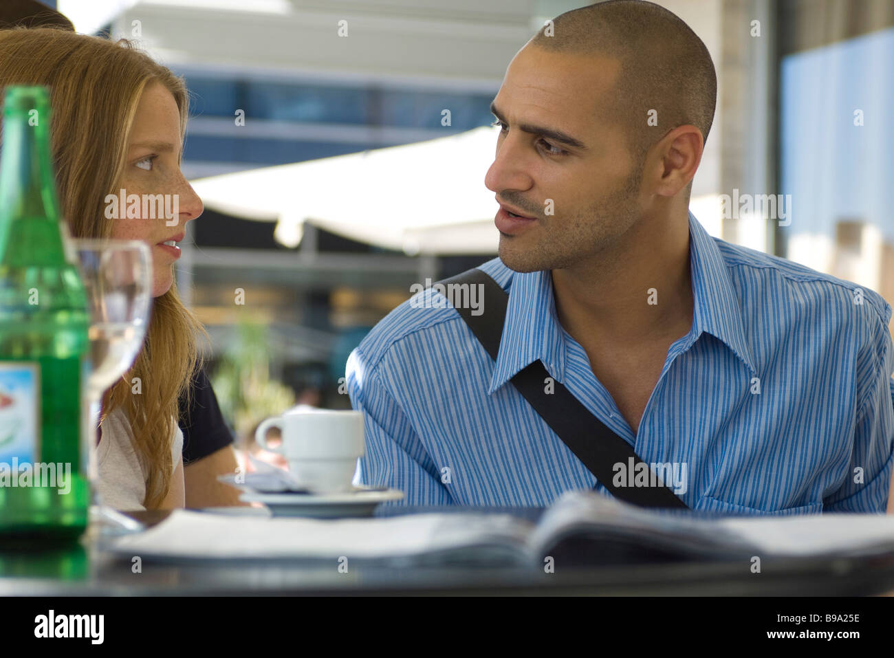 Man and woman sitting in outdoor cafe, having serious conversation - Stock Image