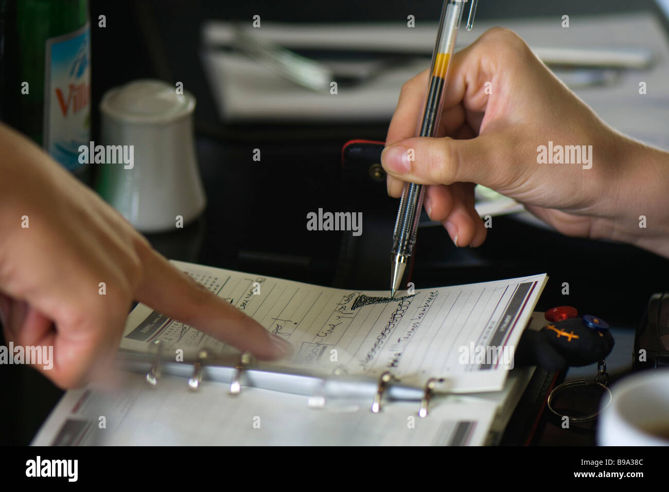 Two people making plans using agenda, one holding pen while the other points to page - Stock Image
