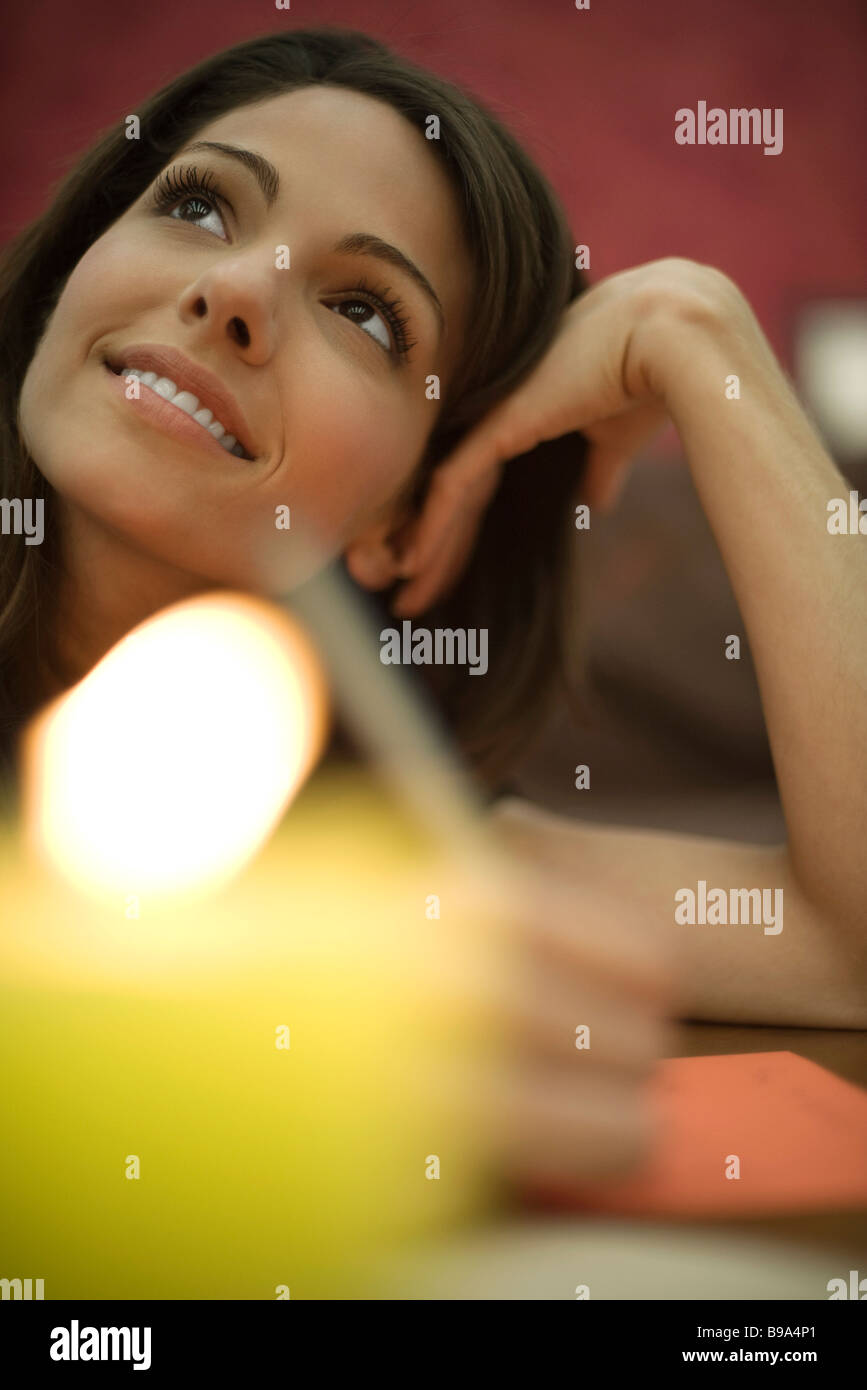 Young woman writing, holding head and looking up, candle in foreground - Stock Image