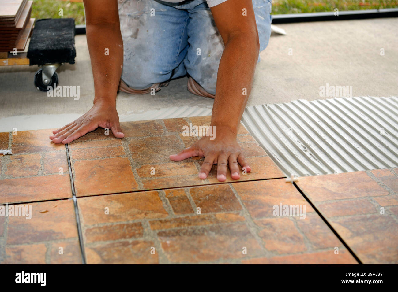 Male hispanic lays ceramic tile on cement floor in patio lanai stock male hispanic lays ceramic tile on cement floor in patio lanai dailygadgetfo Gallery