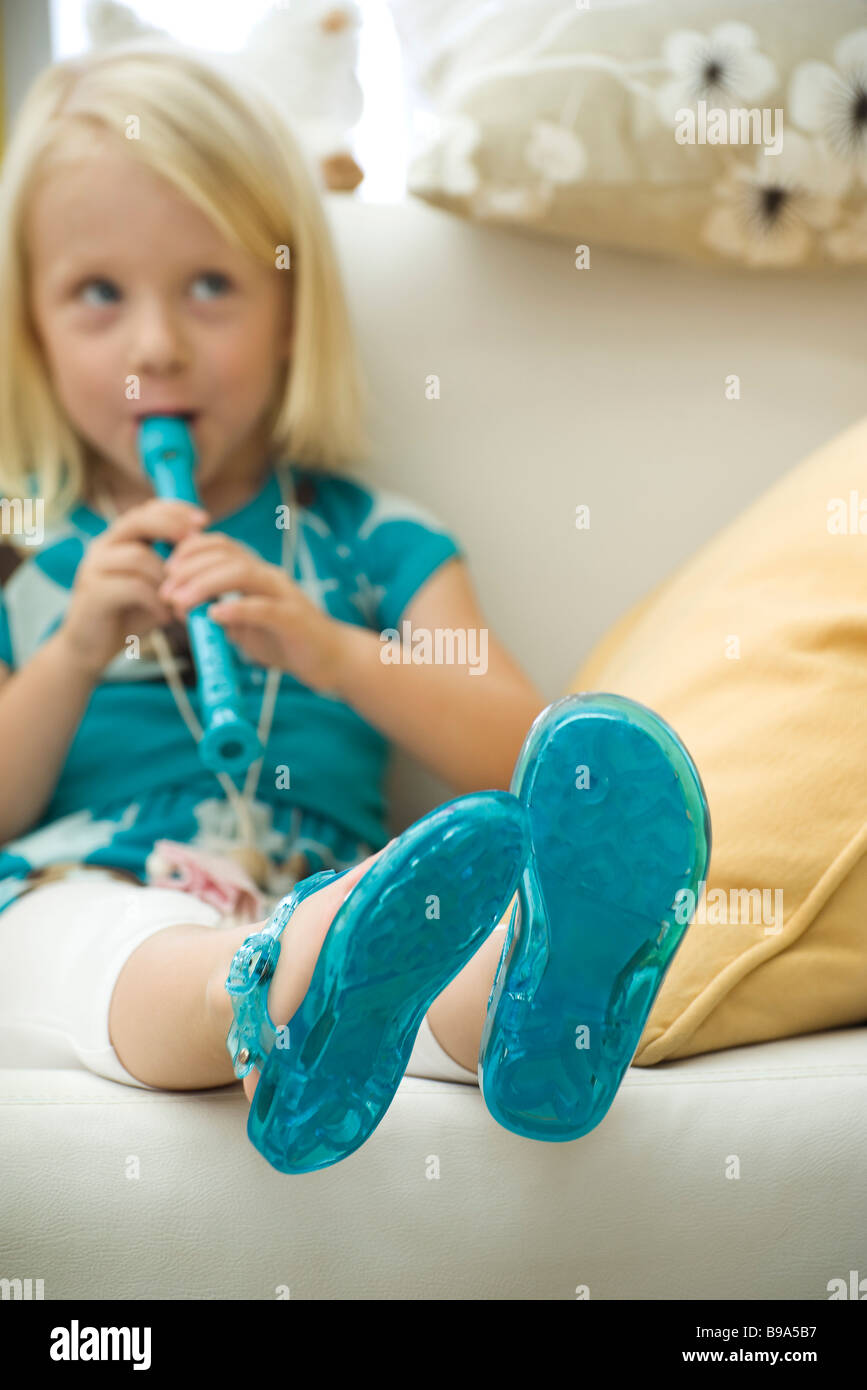 Little girl sitting on sofa, playing recorder - Stock Image