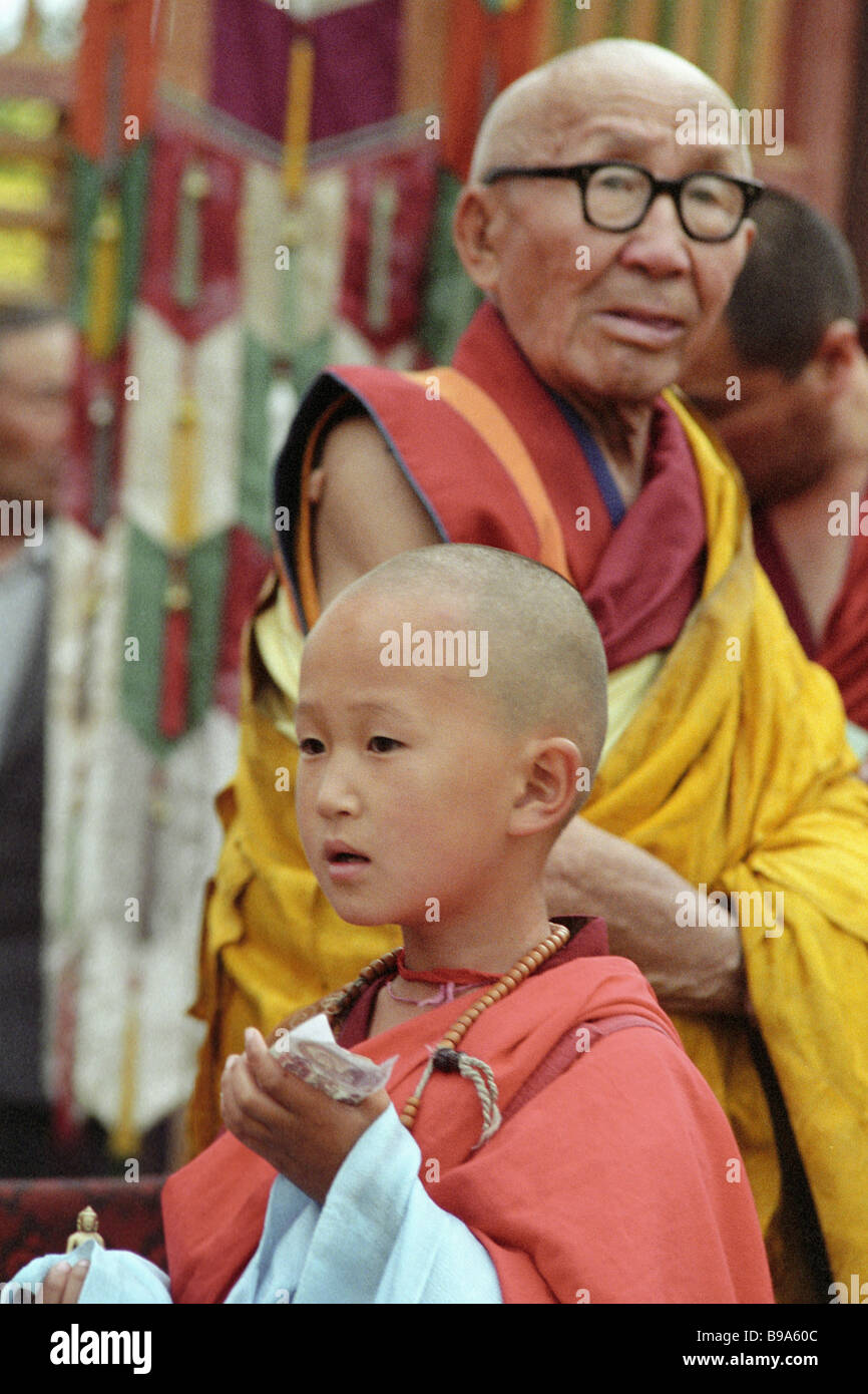 Head of Soviet Buddhists Bandido Khambo lama Tsybikov background and a Buddhist child foreground at the ceremony - Stock Image