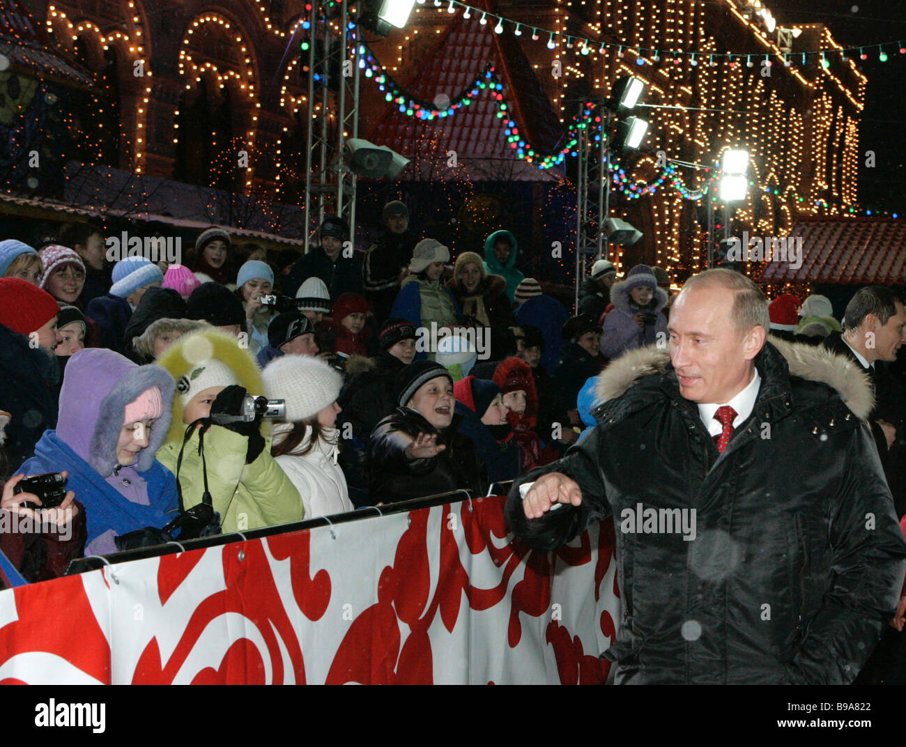 Russian President Vladimir Putin talks to children while visiting the Red Square skating rink next to the Kremlin - Stock Image