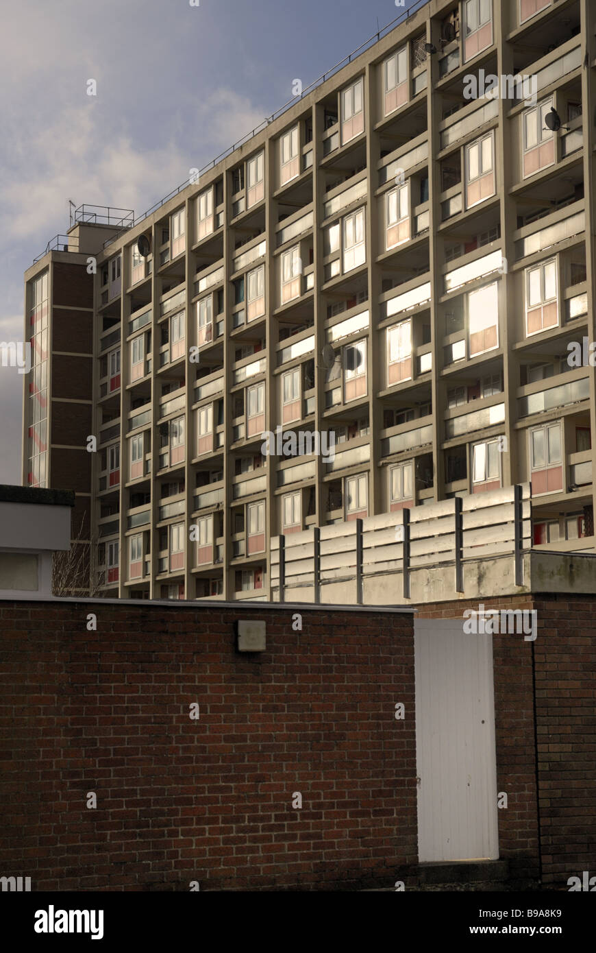 A 1960`s block of flats with light reflecting off windows and a wall and gate in the foreground - Stock Image