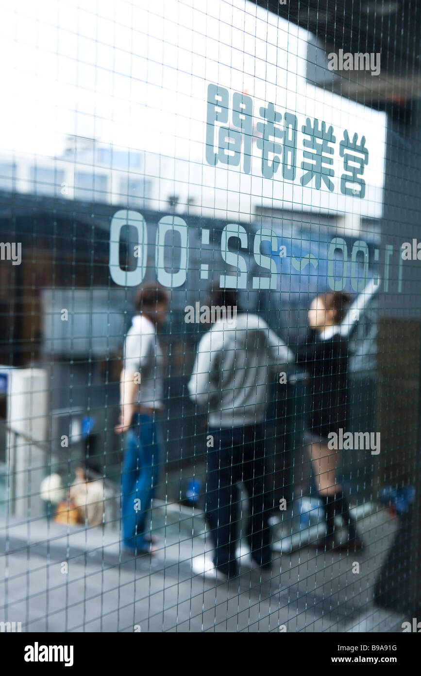 Glass door printed with Japanese text and hours, people standing in background - Stock Image