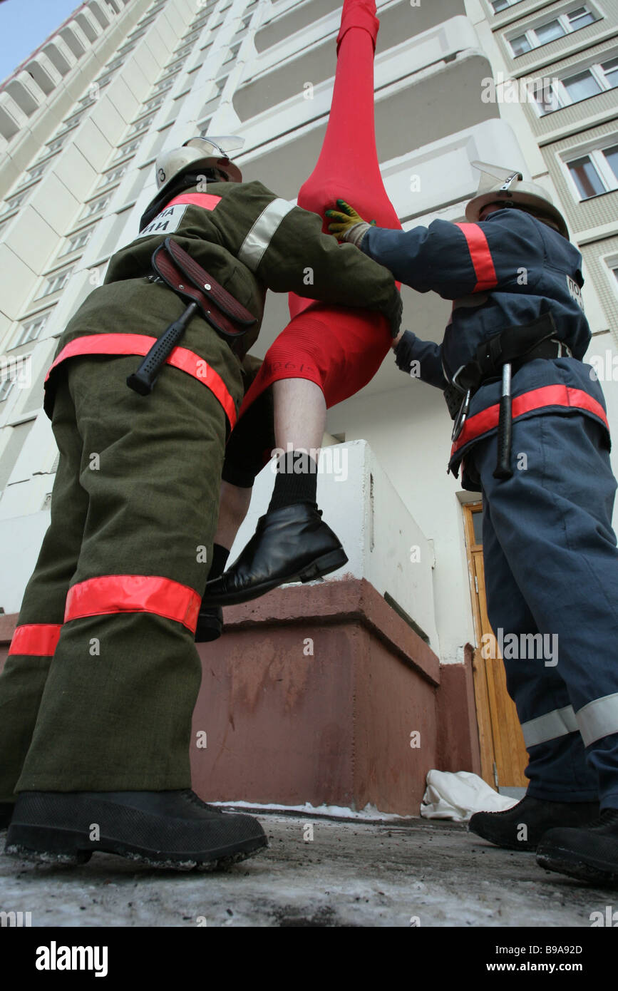 Firemen imitate upper story resident evacuation on a high rise house rescue drill - Stock Image