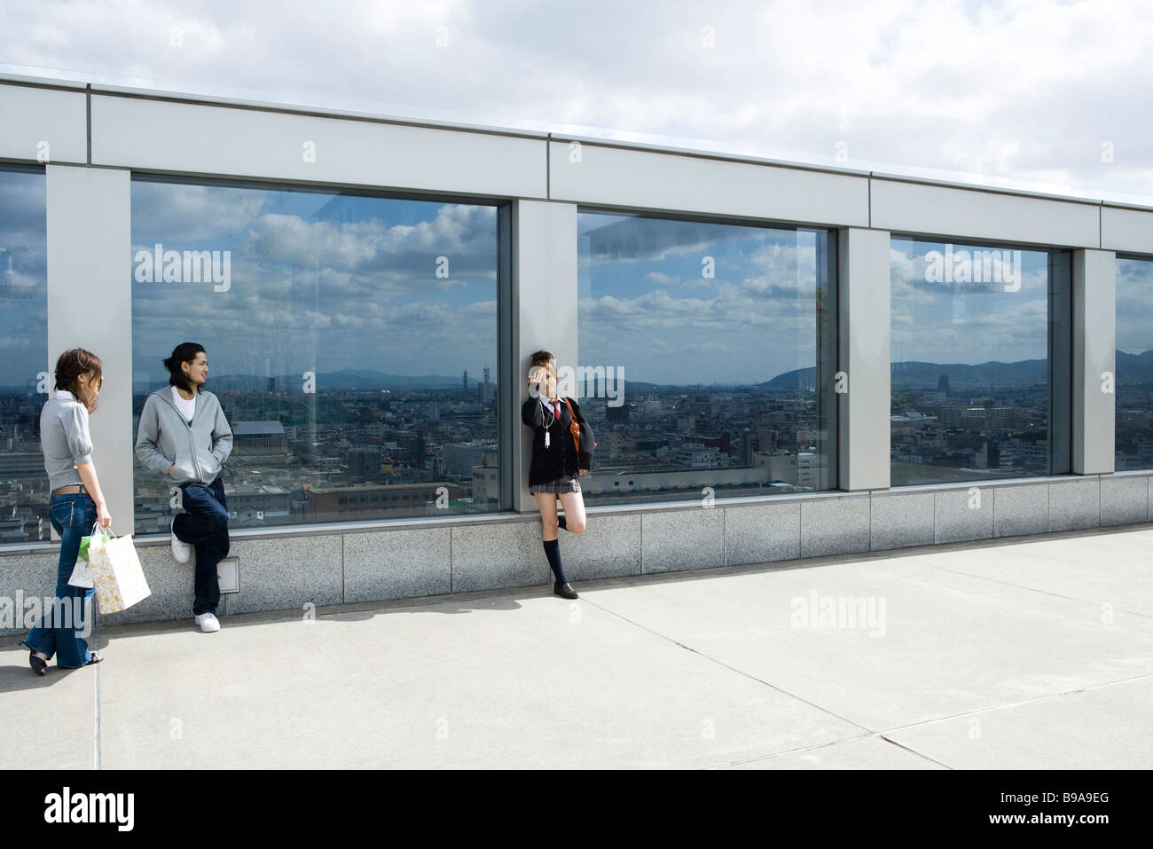 Three young friends leaning against glass wall overlooking city, Kyoto, Japan - Stock Image