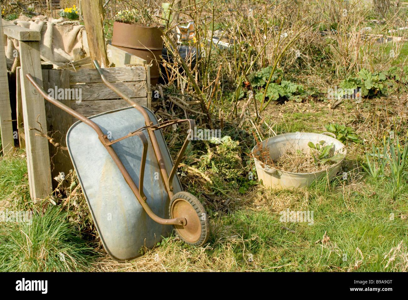 Wheelbarrow in wild garden - Stock Image
