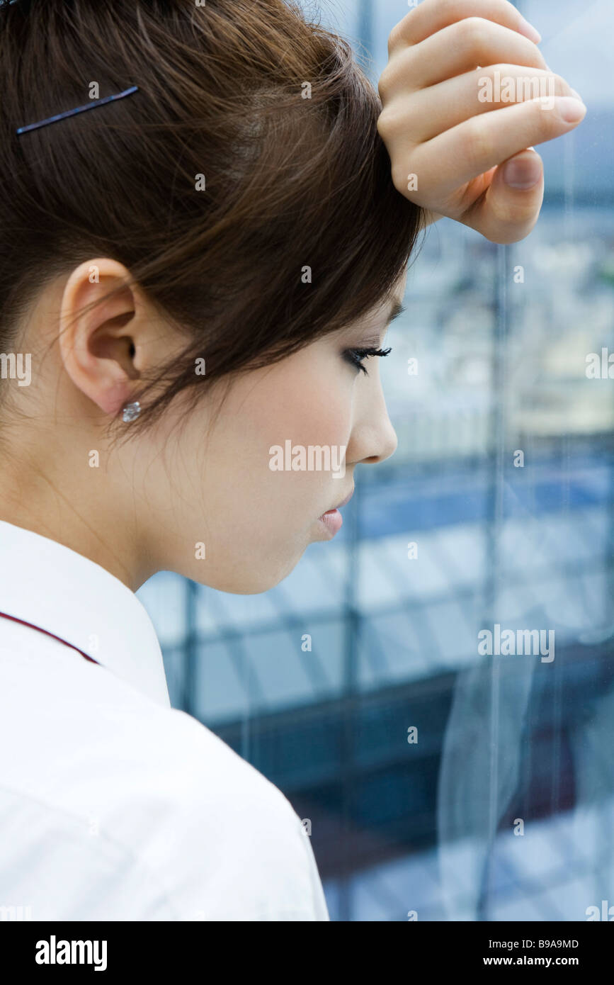 Young female resting head on arm against window, looking out, side view - Stock Image