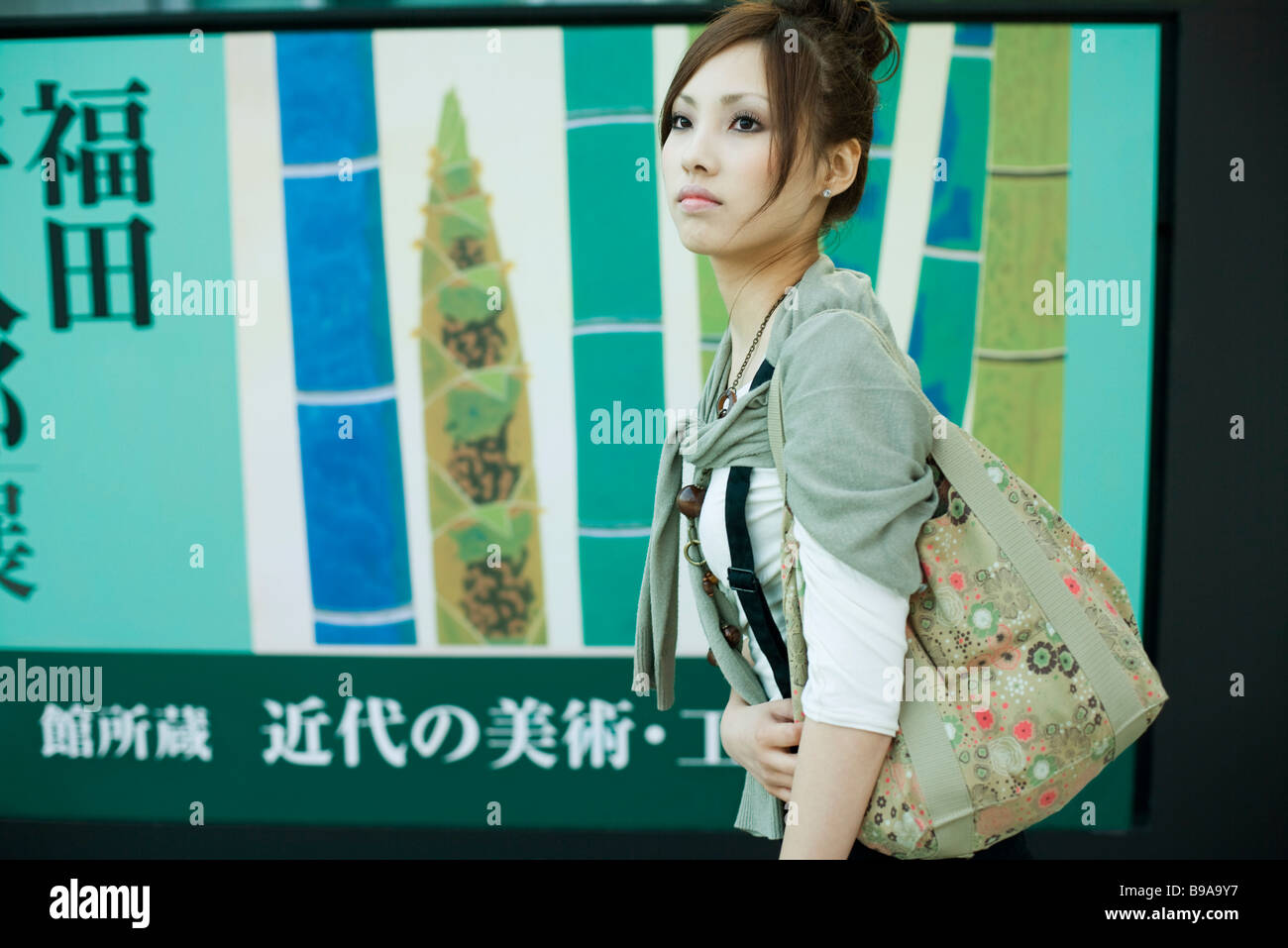 Young female walking past large poster with Japanese script, side view - Stock Image