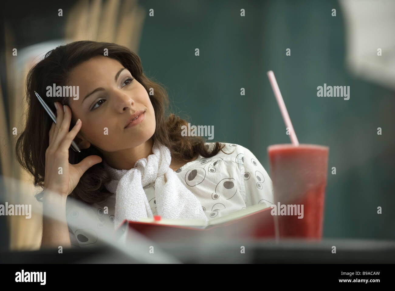 Woman sitting in cafe with notebook, holding head - Stock Image