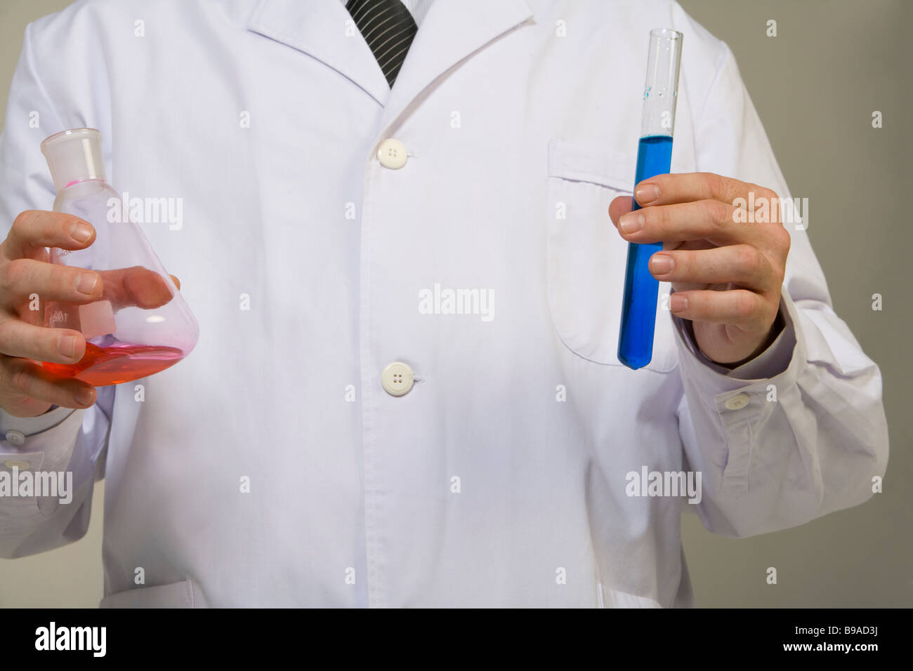 Close up of scientist holding beakers - Stock Image