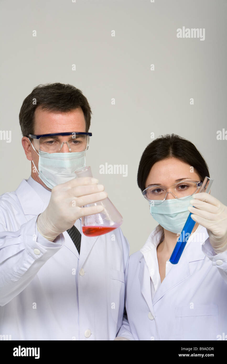 Scientists examining liquids in beakers - Stock Image