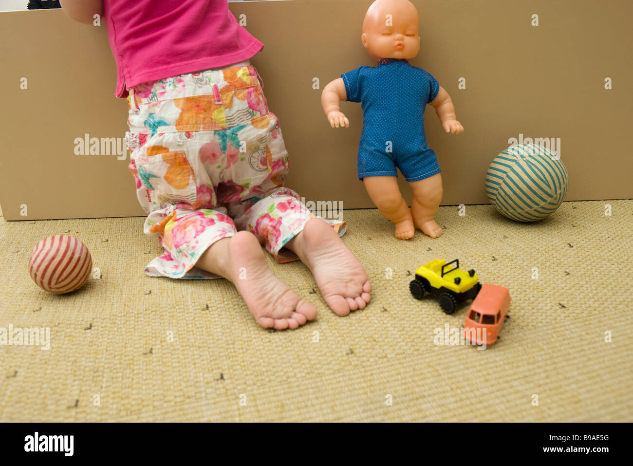 Little girl kneeling on floor with toys, rear view, cropped - Stock Image