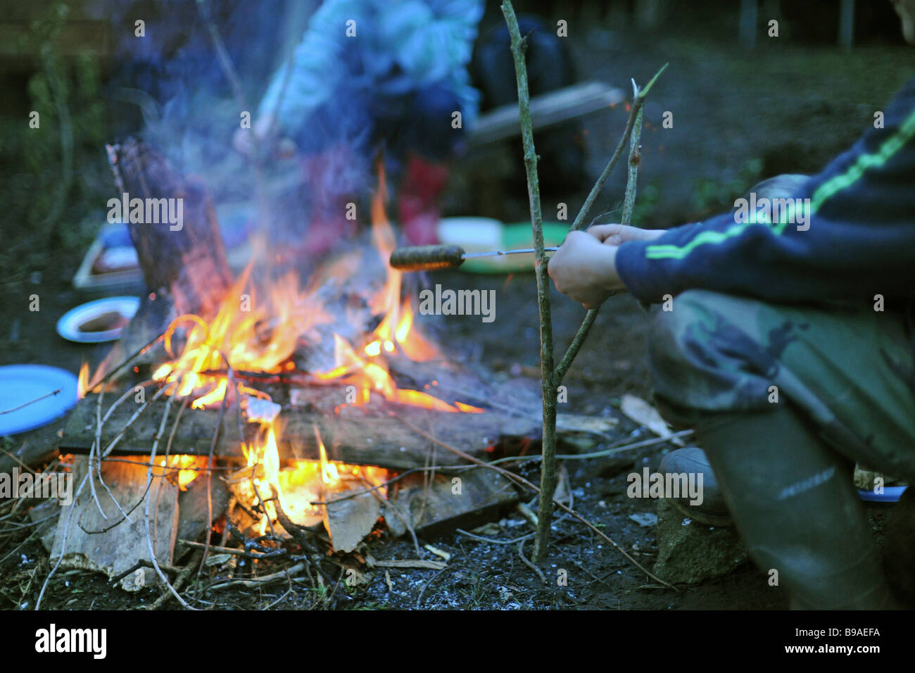 Boy cooking sausage on fire - Stock Image