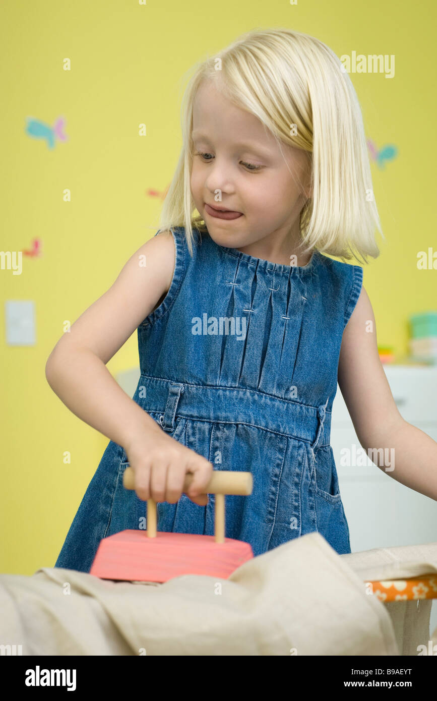 Little girl playing with toy iron and ironing board - Stock Image