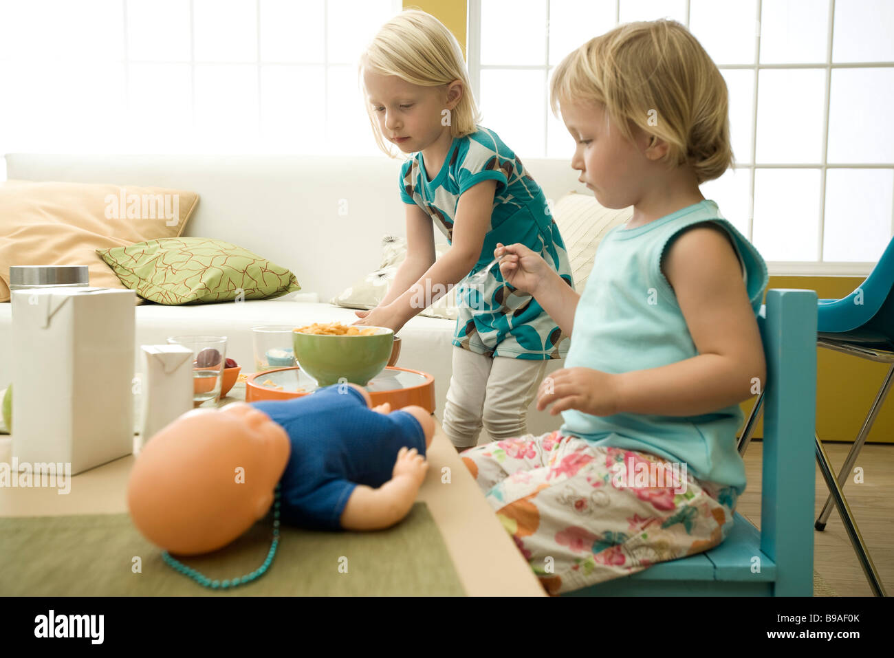 Little girls eating cereal at messy table - Stock Image