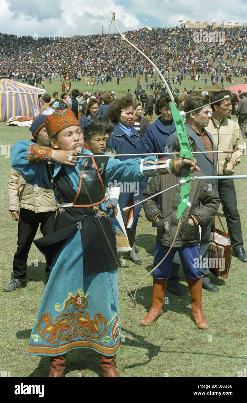 Local girl in national dress practicing archery Stock Photo