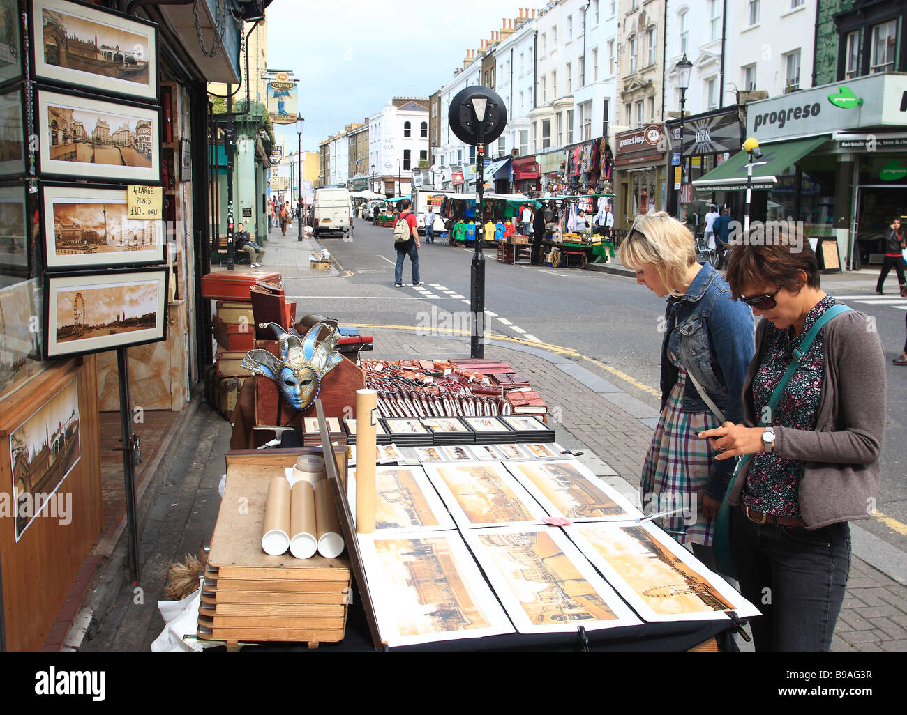 Tourists looking at display outside an Antique shop in Portobello Road,London,England. - Stock Image