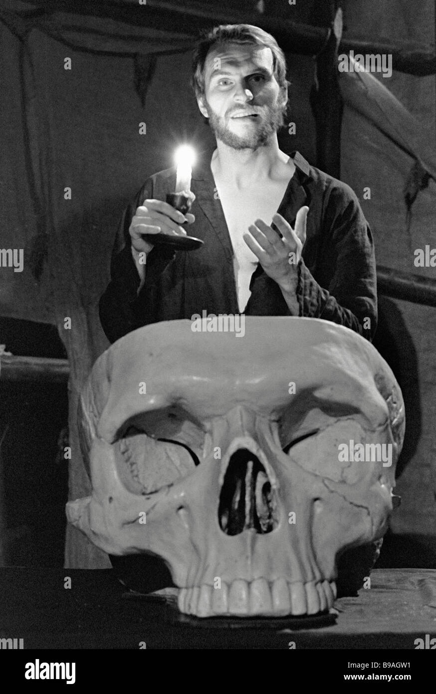 Actor starring as Hamlet stands with candle near skull Scene from play Hamlet at Vstrecha Theater - Stock Image