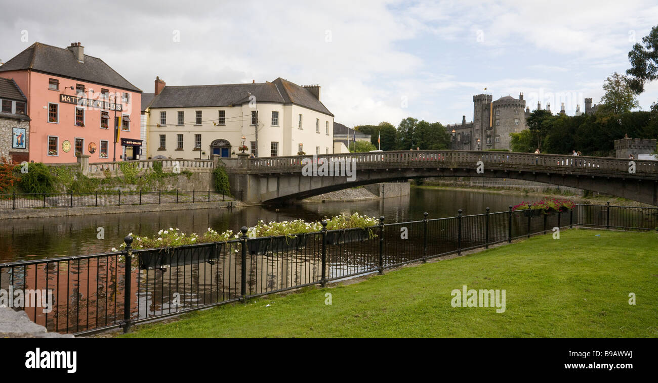 Kilkenny City. A few tourists cross the Lower John Street bridge over the River Nore with the castle in the background. - Stock Image