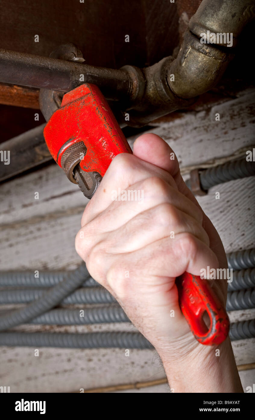 A hand on a pipe wrench or Stillson wrench tightening pipes in house plumbing. - Stock Image