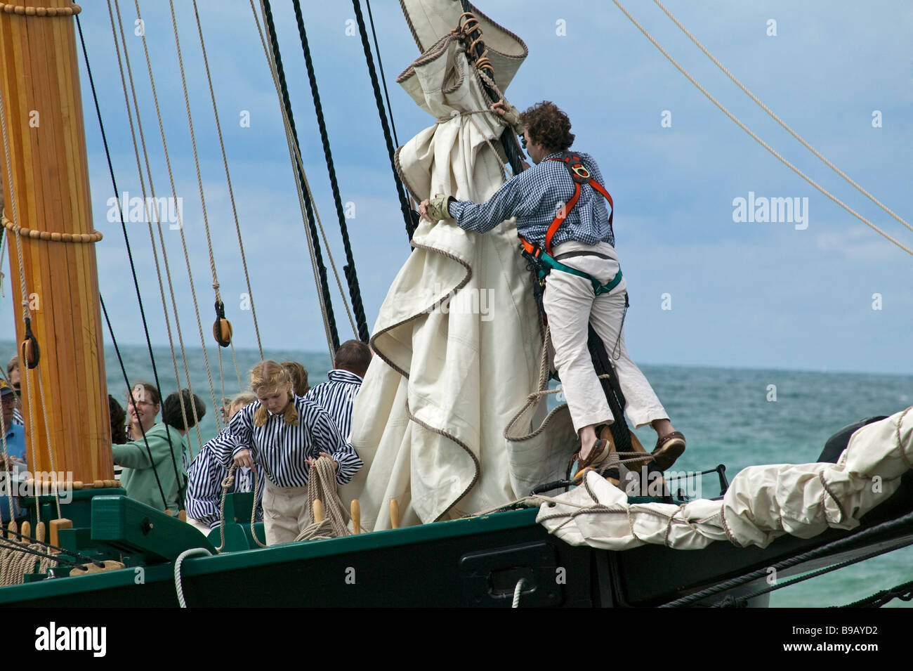 Furling the sails as the historic tall ship 'Friends Good Will' arrives in South Haven, Michigan on her - Stock Image