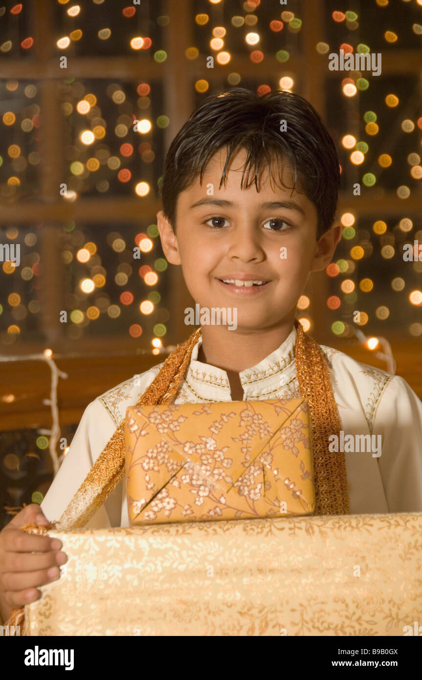 Boy holding Diwali gifts and smiling - Stock Image