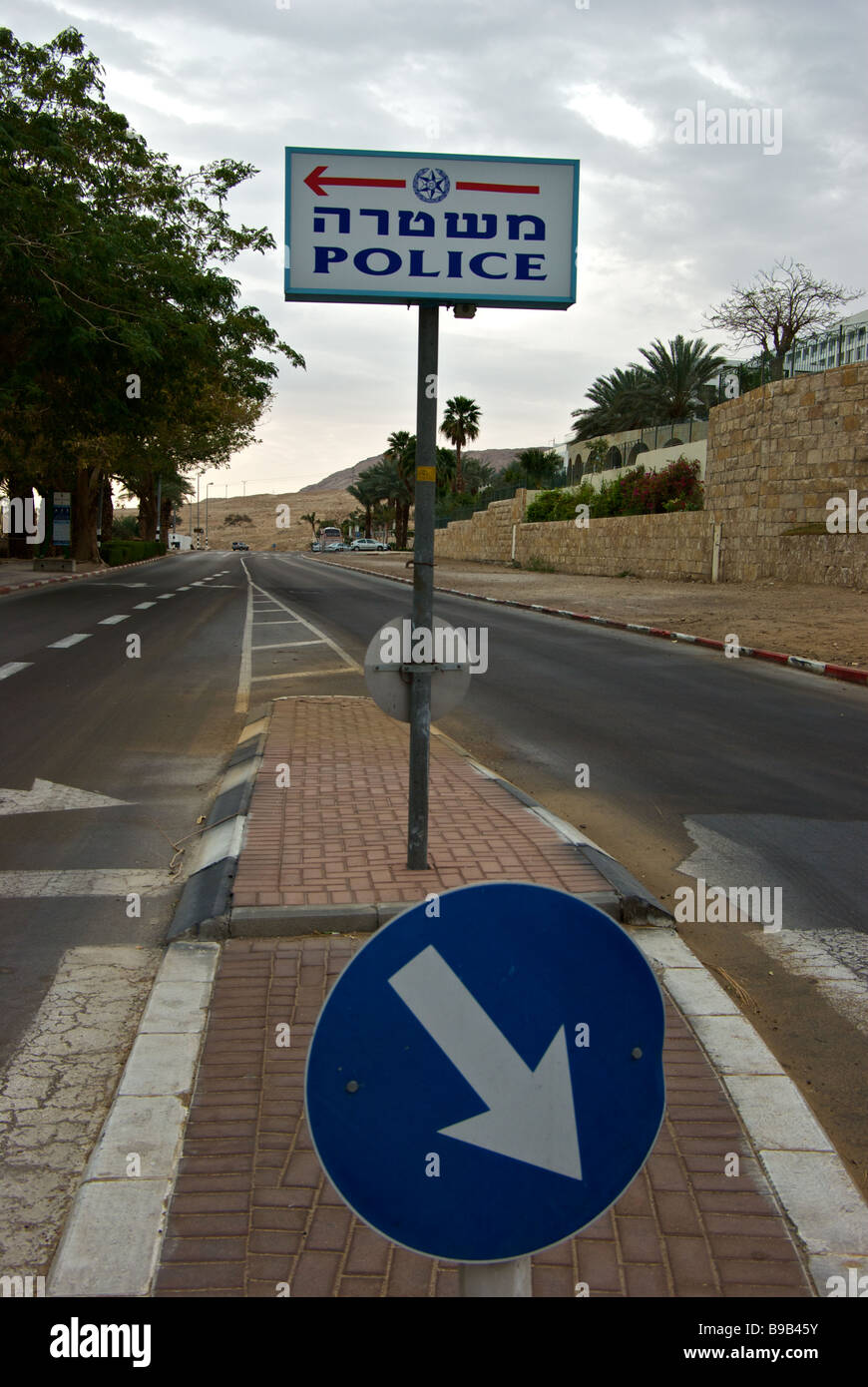 Sign in Hebrew and English on centre median of waterside drive indicating location of police station - Stock Image