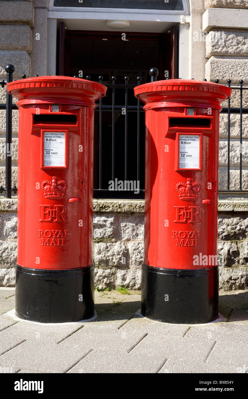Two colourful red British postboxes outside Falmouth Post Office. - Stock Image