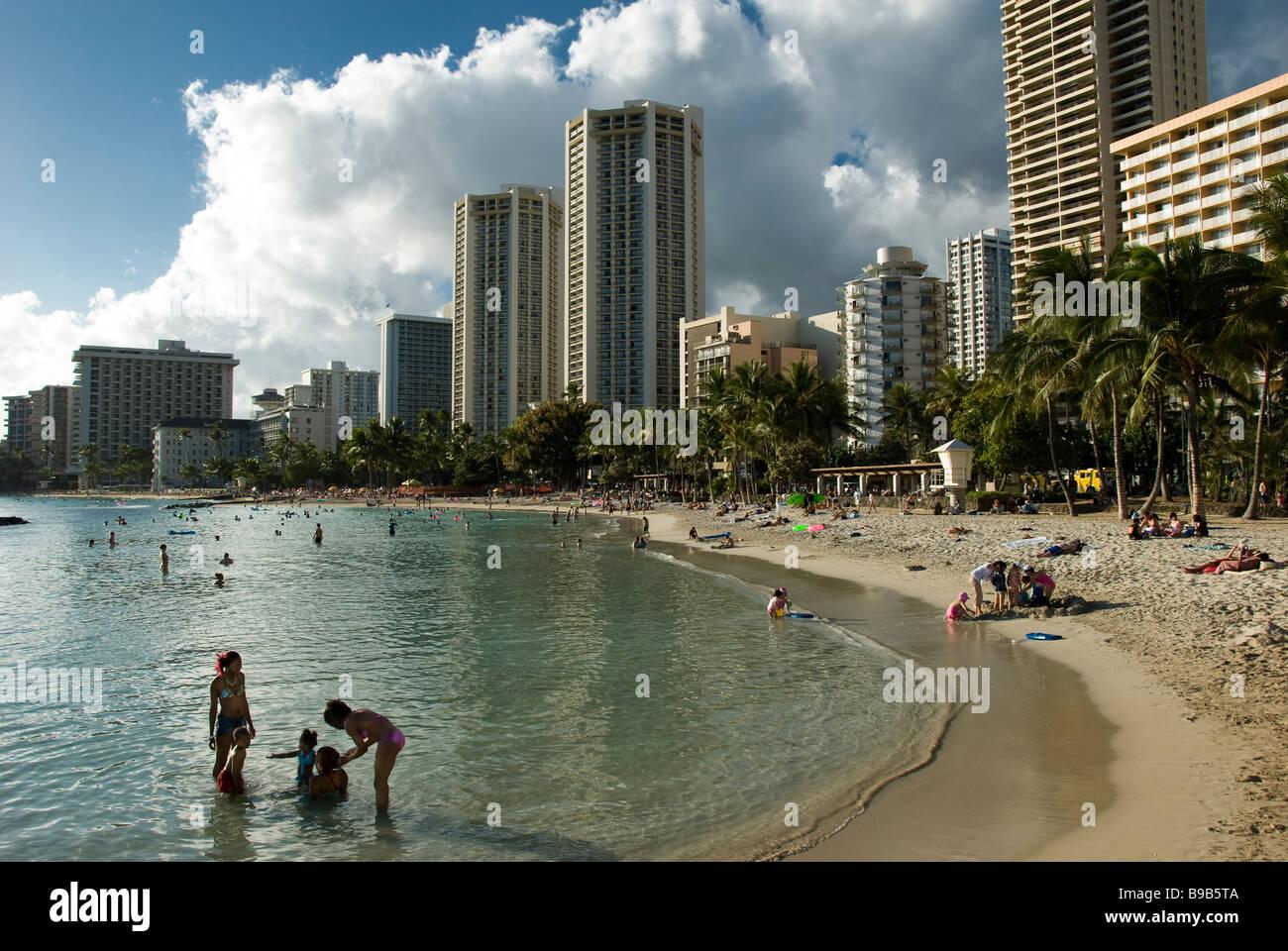 Families enjoy the sand, Waikiki Beach, Honolulu, Oahu, Hawaii. Stock Photo