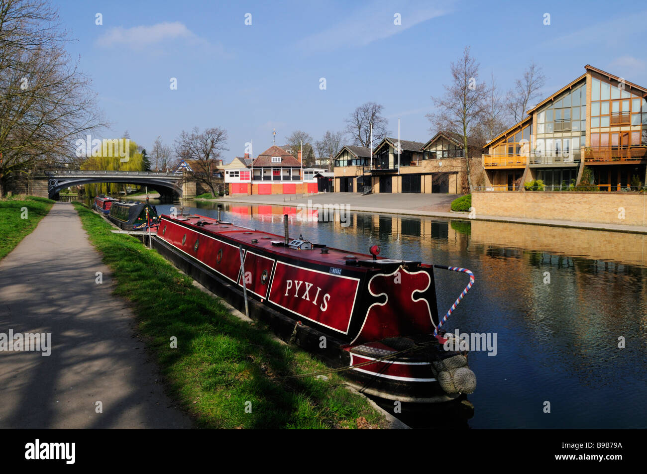 Narrowboats moored on the River Cam at Midsummer Common, with  rowing boathouses on the far bank,  Cambridge England - Stock Image