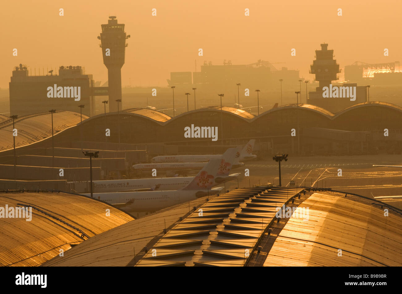 Smog shrouds Hong Kong Chek Lap Kok Airport at sunset. - Stock Image