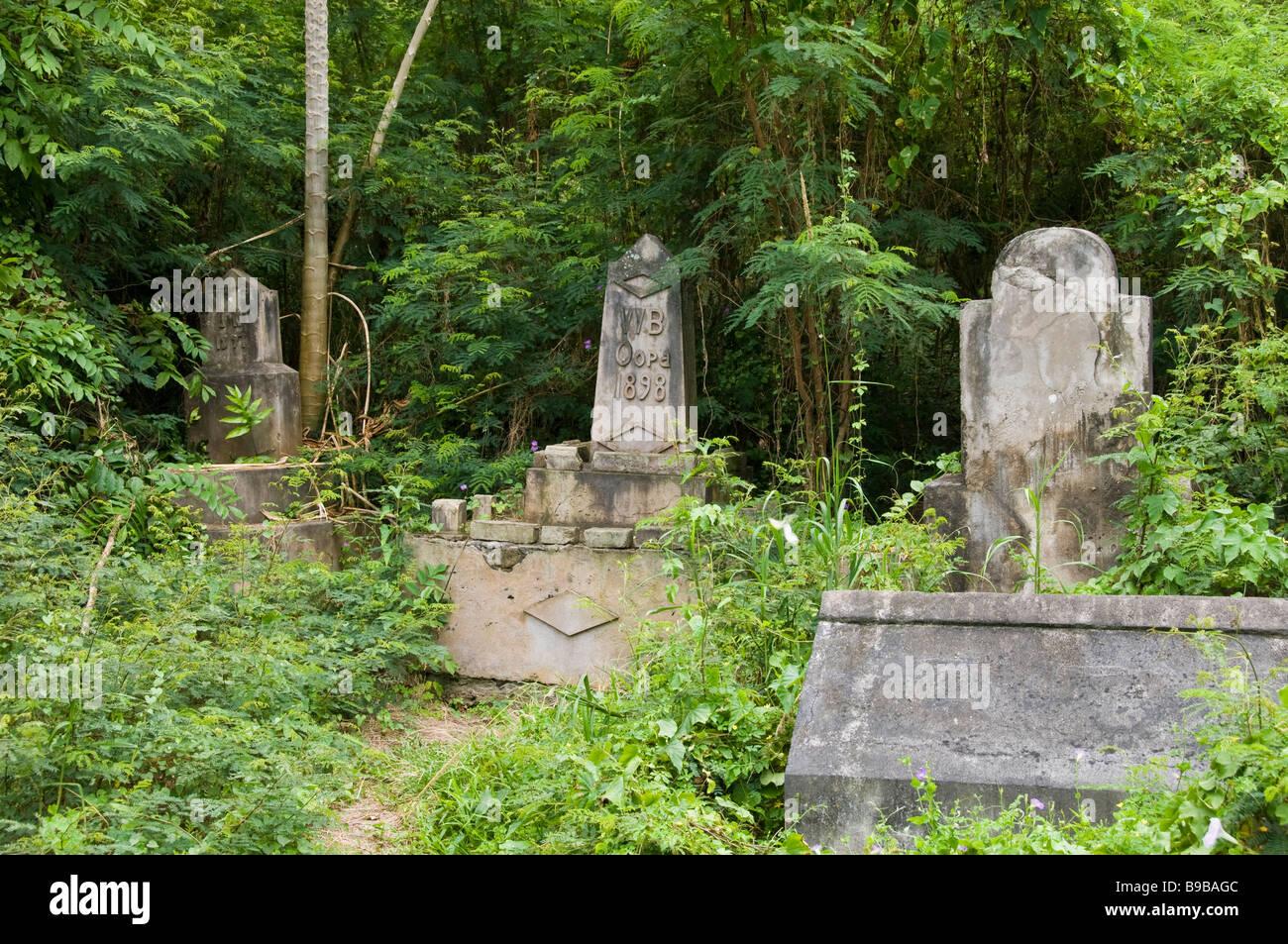 Tombstones behind abandoned building, Halawa Valley, Molokai, Hawaii. - Stock Image