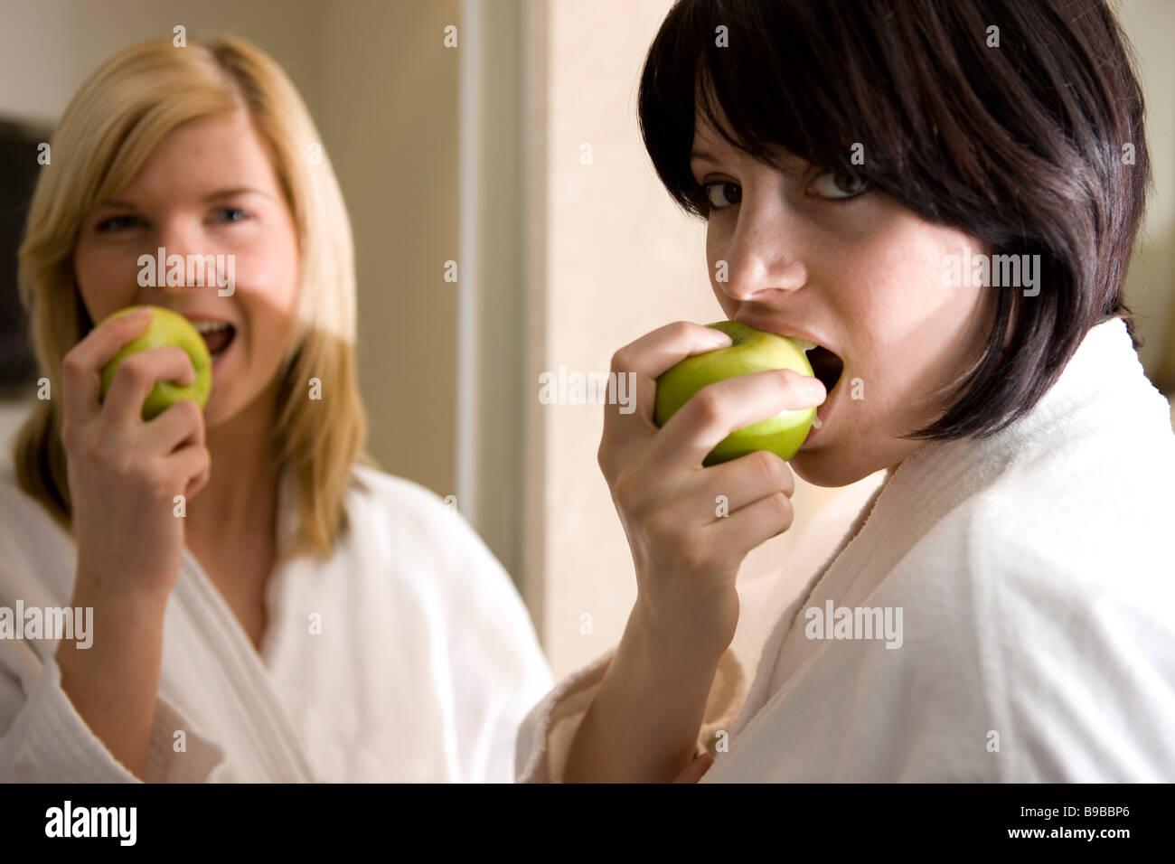 zwei frauen essen/ beissen in einen apfel Stock Photo