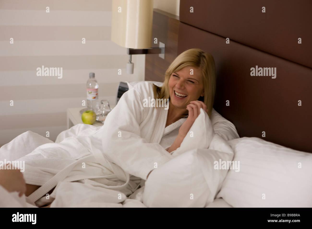 frau liegt lachend im bademantel auf dem bett Stock Photo