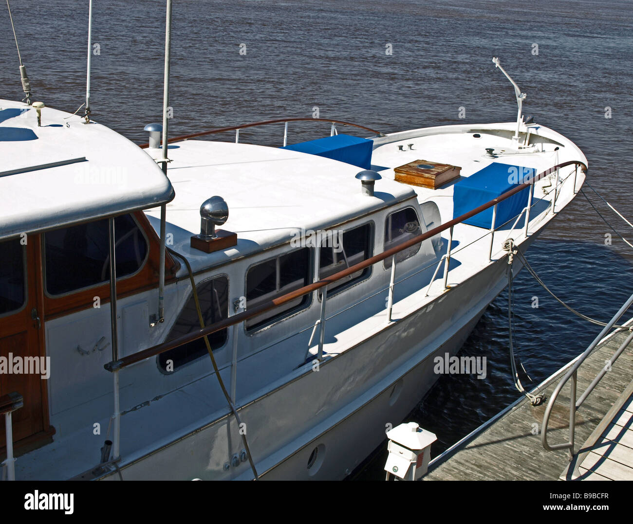 power boat vessel yacht at dock in river with panelled cabin and white decks - Stock Image