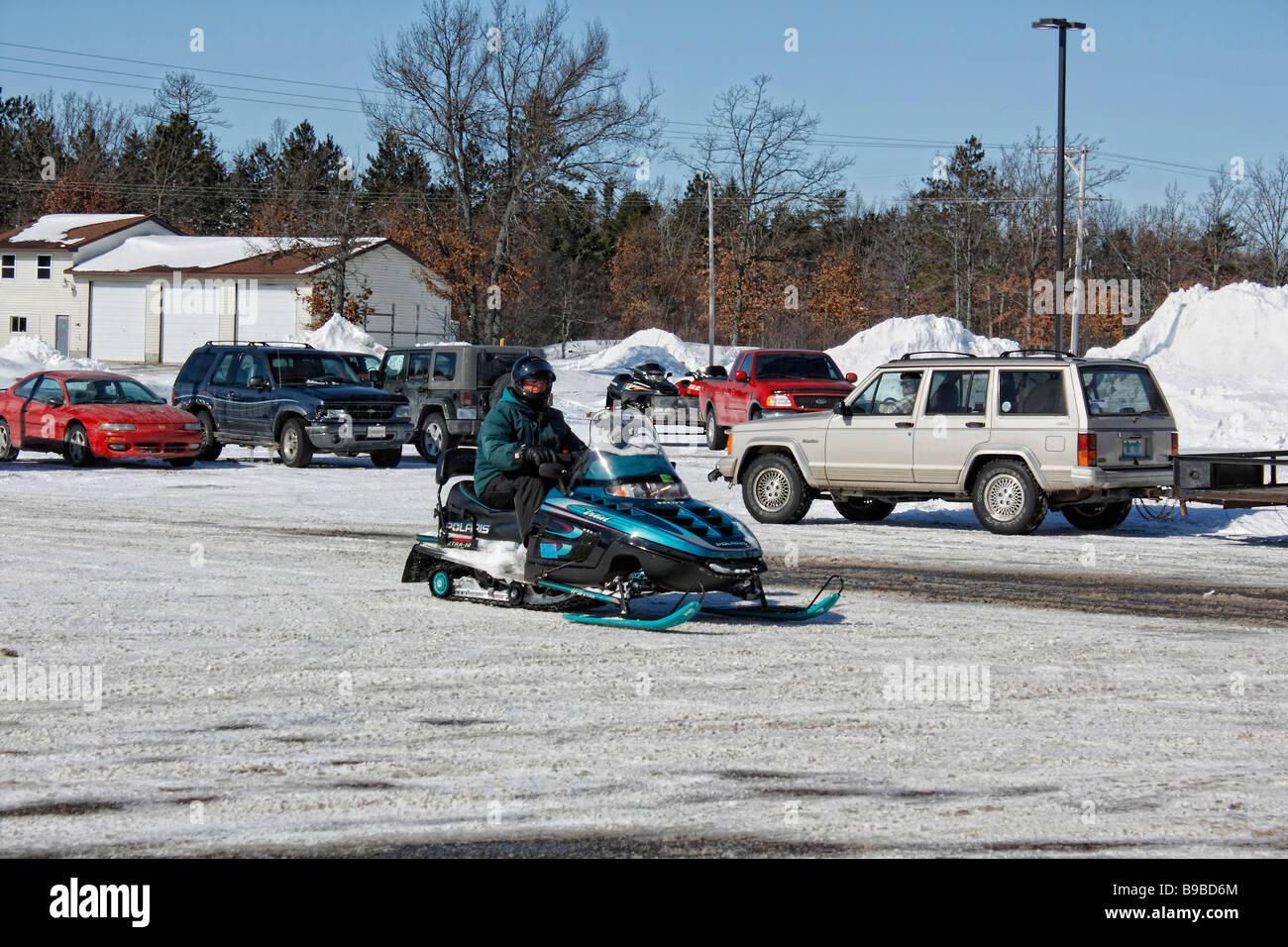 Snowmobile with snowmobiler on the city Michigan USA - Stock Image