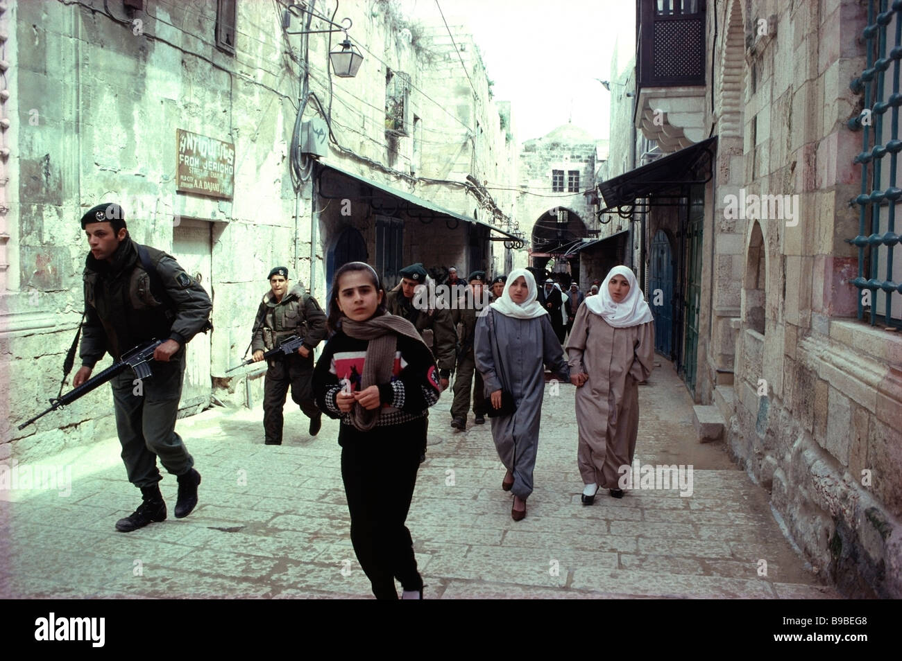 Palestinian School girl followed by two Palestinian women and Israeli soldiers on the Street of the Chain in Jerusalem,Israel. - Stock Image