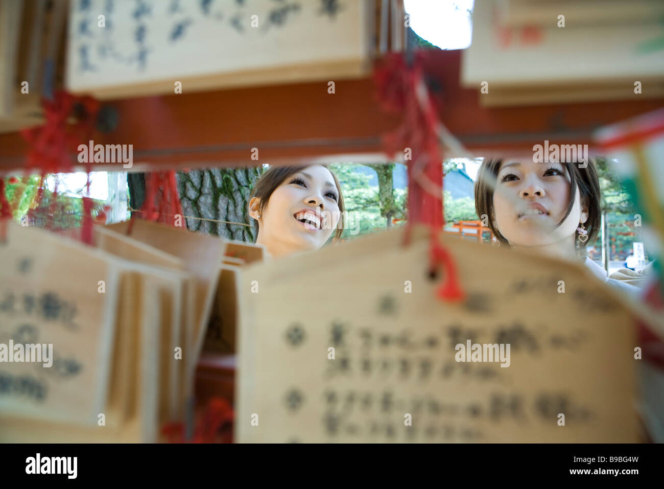Young females looking at traditional Japanese ema wishes in Shinto shrine - Stock Image