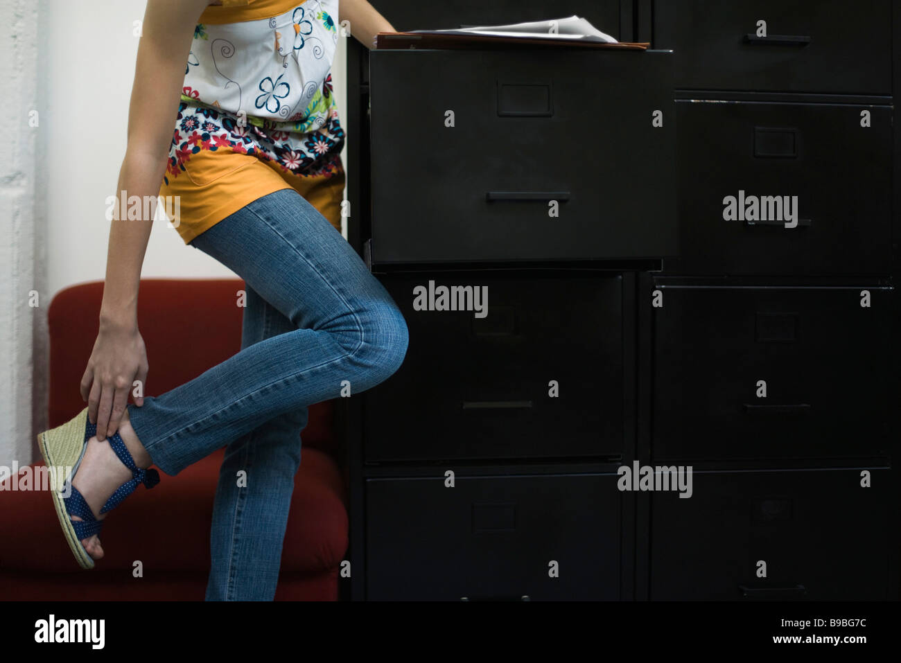 Woman adjusting shoe, leaning against filing cabinet - Stock Image
