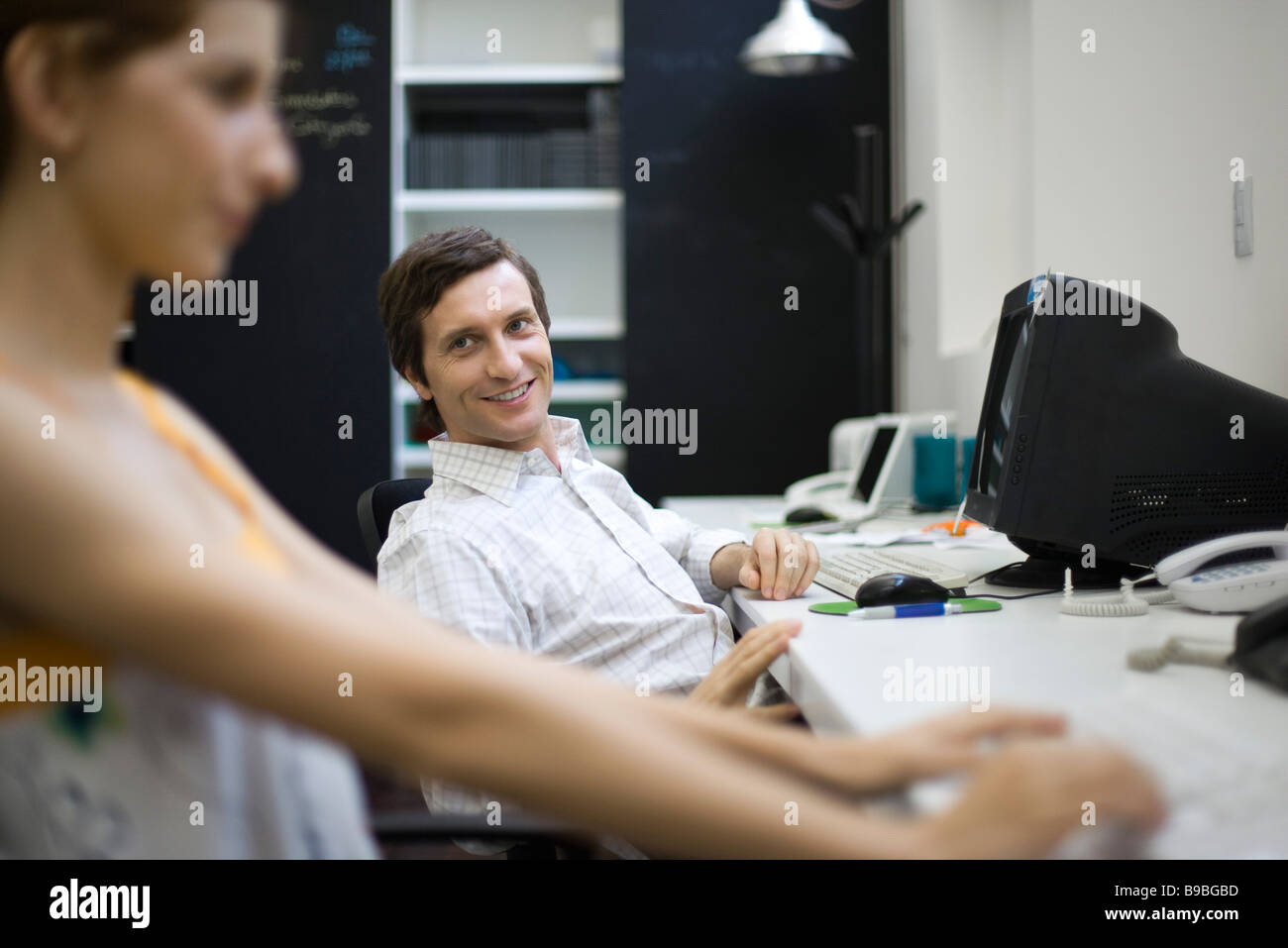 Man sitting at desk, smiling at female colleague - Stock Image