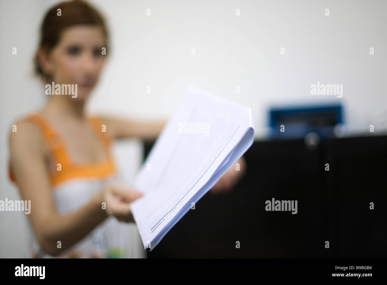 Woman holding out document, focus on foreground - Stock Image