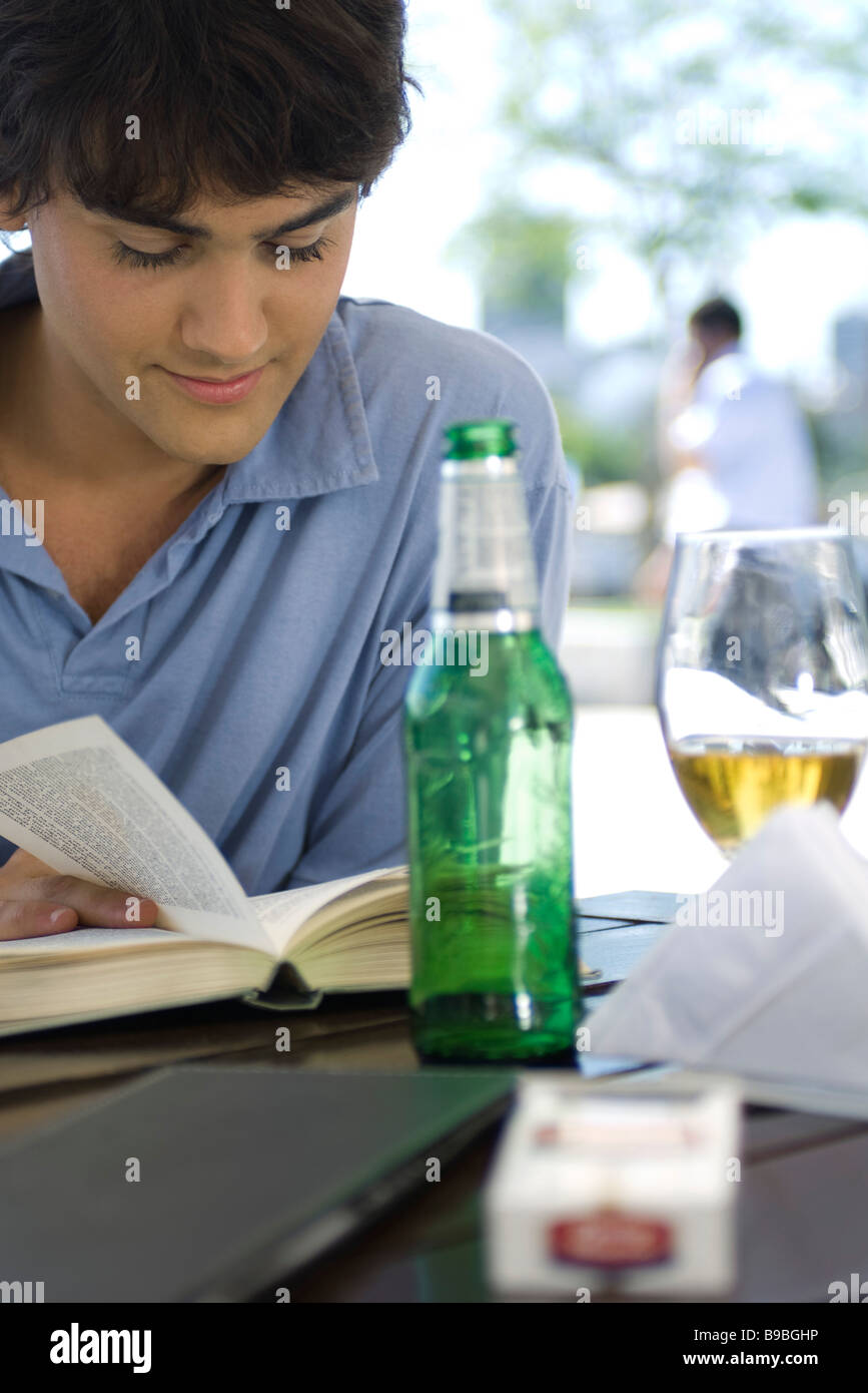 Young man reading book and having a beer at an outdoor cafe - Stock Image