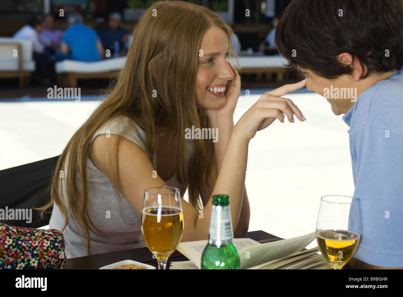 Young couple flirting in outdoor cafe - Stock Image